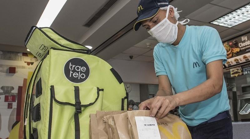 Hombre de servicio delivery venezolano preparando paquete