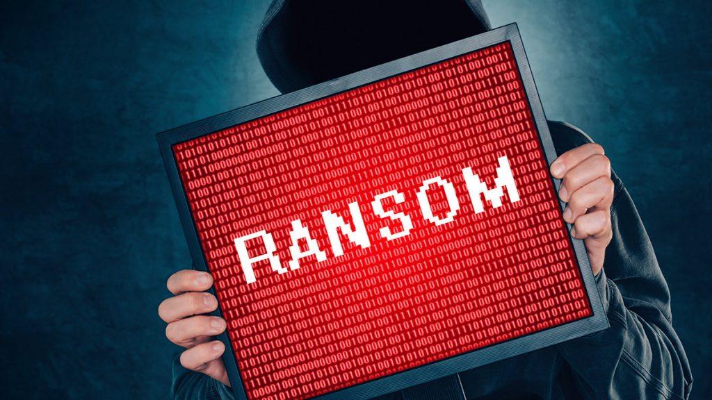 hombre enmascarado con anuncio de ransomware